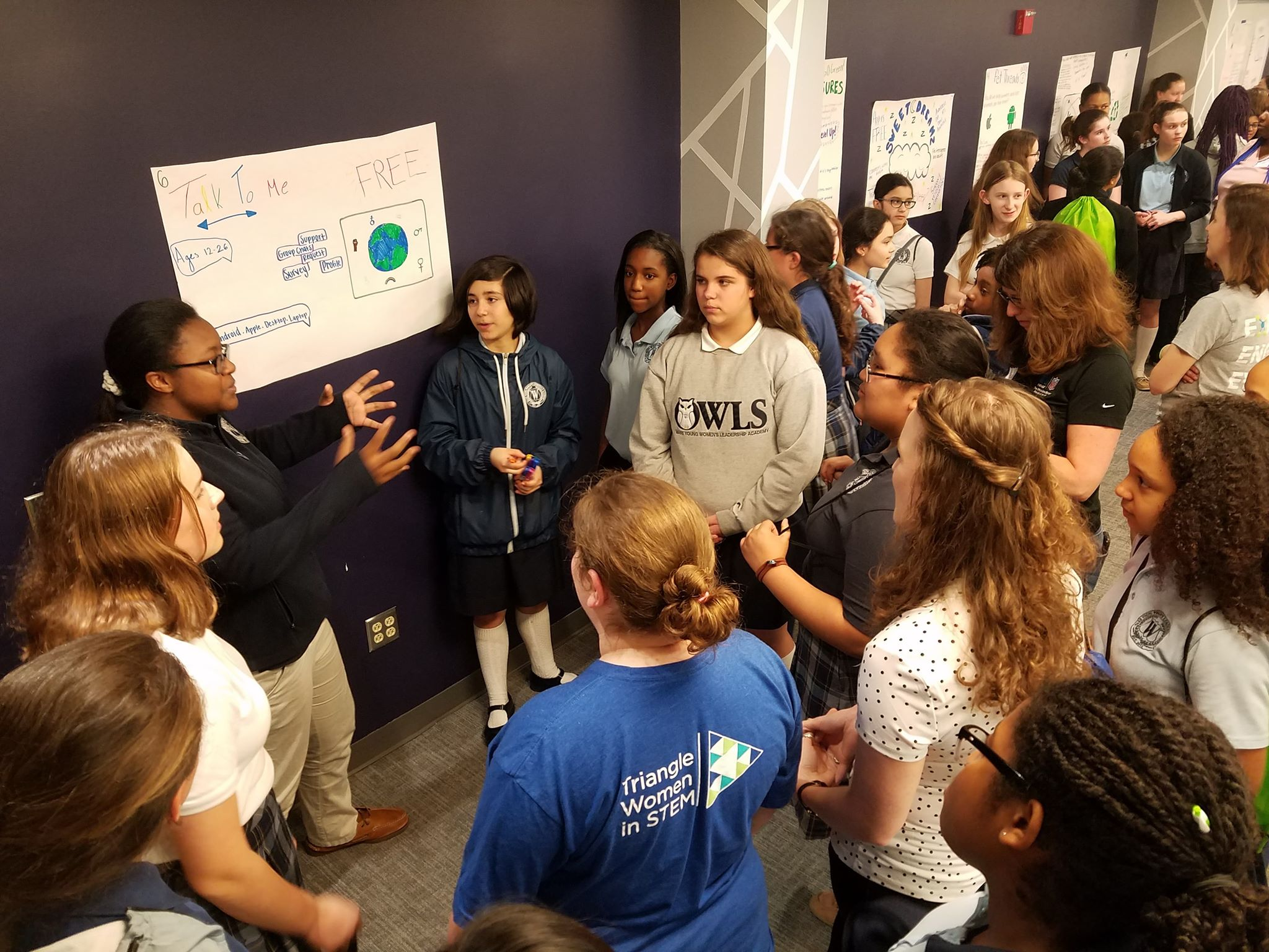 Girl presents poster with her app idea to a group of her peers