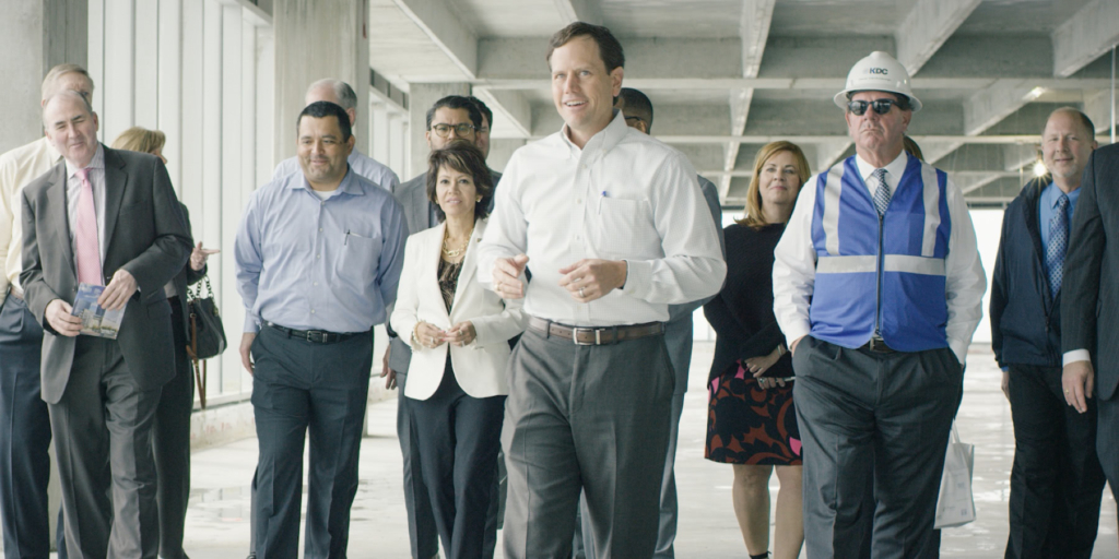A large group of employees and top talent walking together through a concrete industrial space.