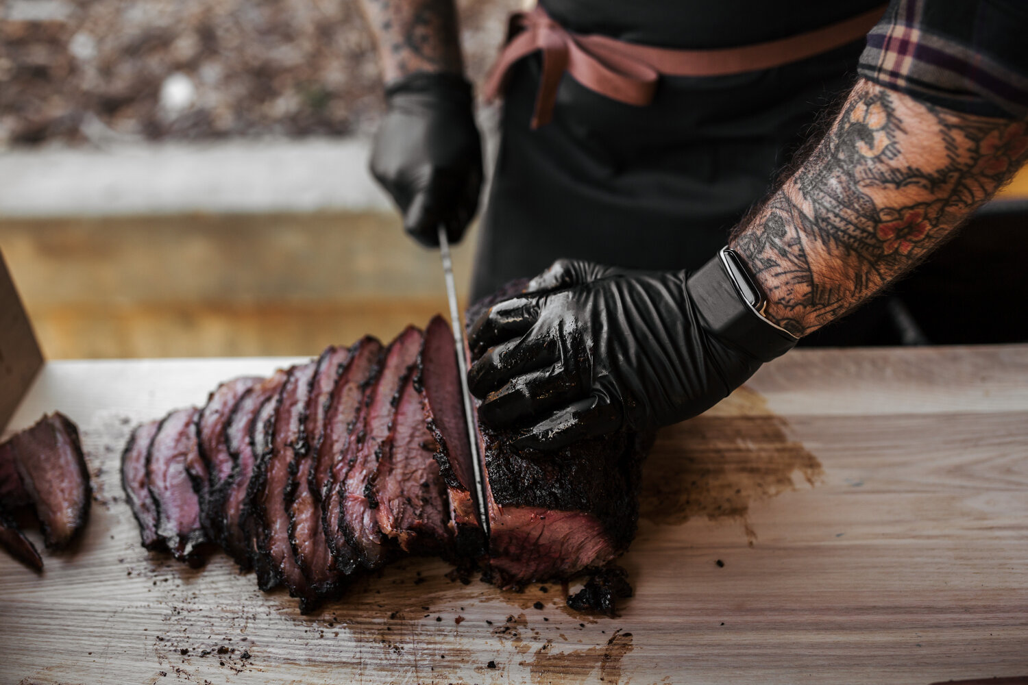 Pitmaster cutting through a piece of barbaque.