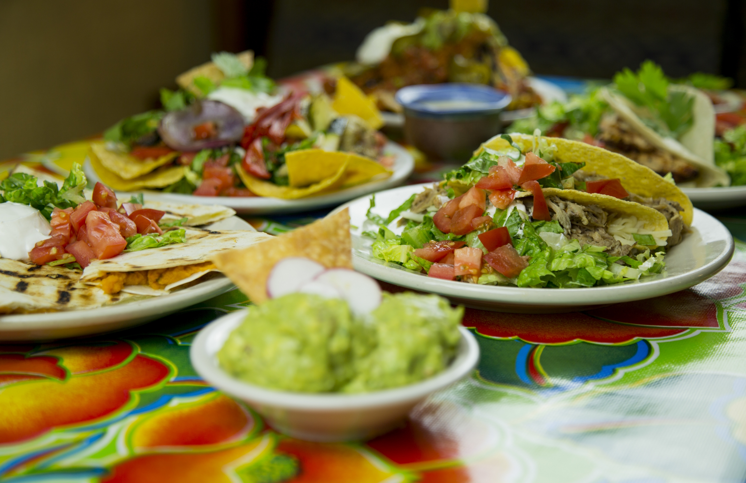 Various tacos on plates sides like guacamole and chips and salsas.
